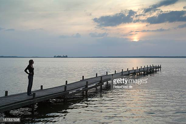 Young woman standing on lakeside jetty watching sunset (XXL)