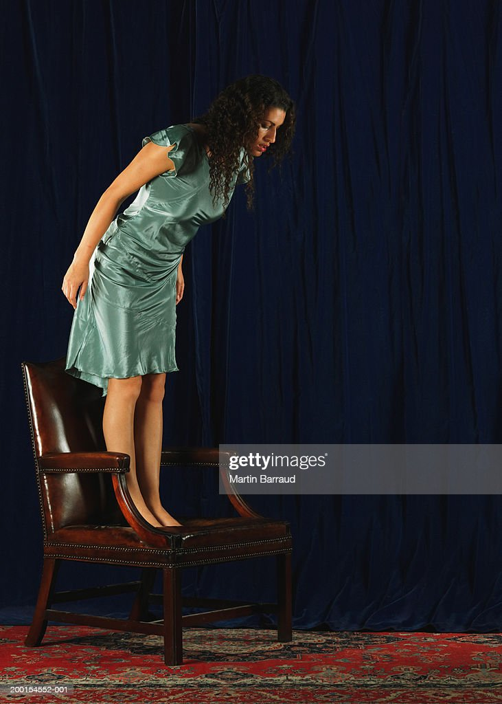 Young woman standing on leather chair, looking at floor : Stock Photo