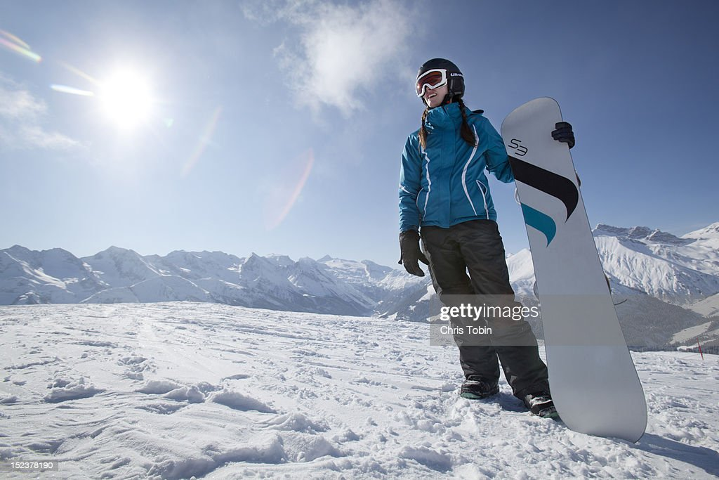 Young woman standing on mountain with her snowboar : Stock Photo