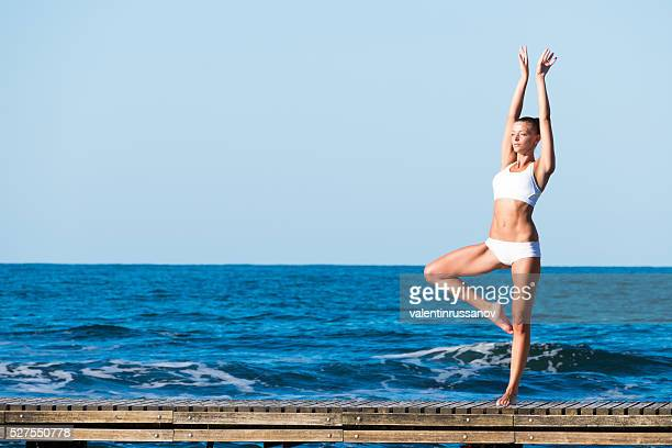 Young woman standing on pier in yoga pose
