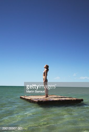 Young woman standing on raft, looking up