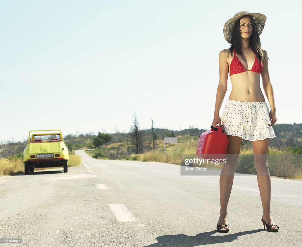 Young woman standing on road holding gas can : Stock Photo