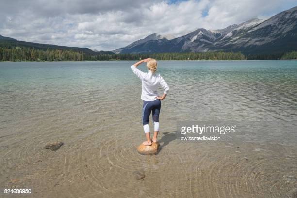 Young woman standing on rock above lake