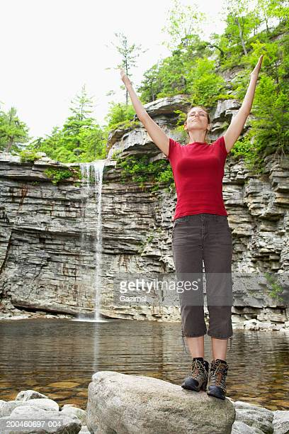 Young woman standing on rocks in river with hands in air