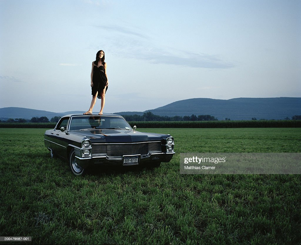 Young woman standing on roof of vintage car in field : Stock Photo