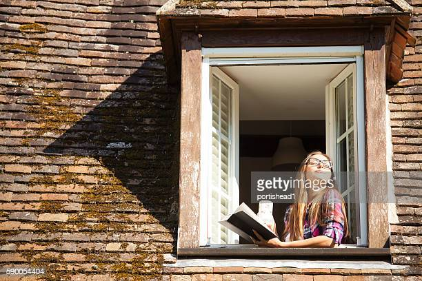 Young woman standing on rooftop window and reading a book