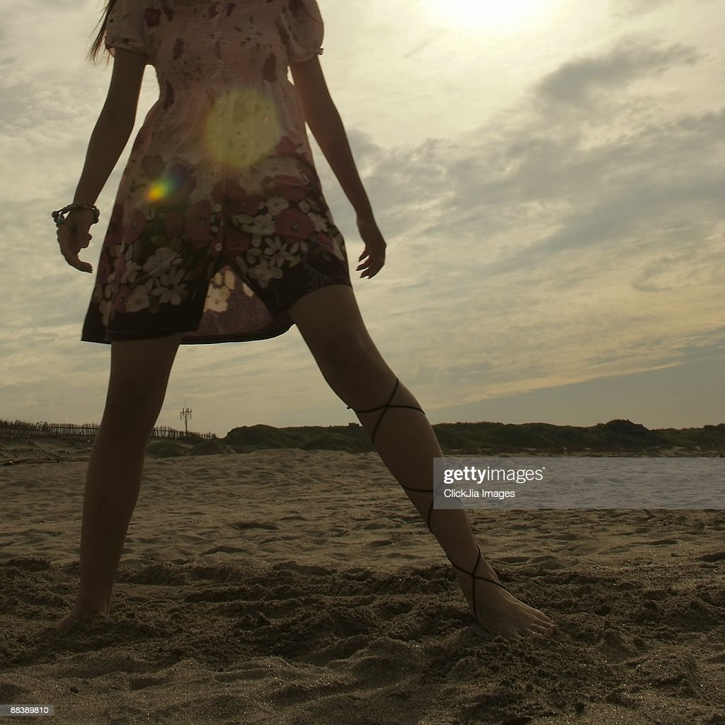 Young woman standing on sand at sunset