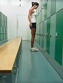 Young woman standing on scales in locker room, side view