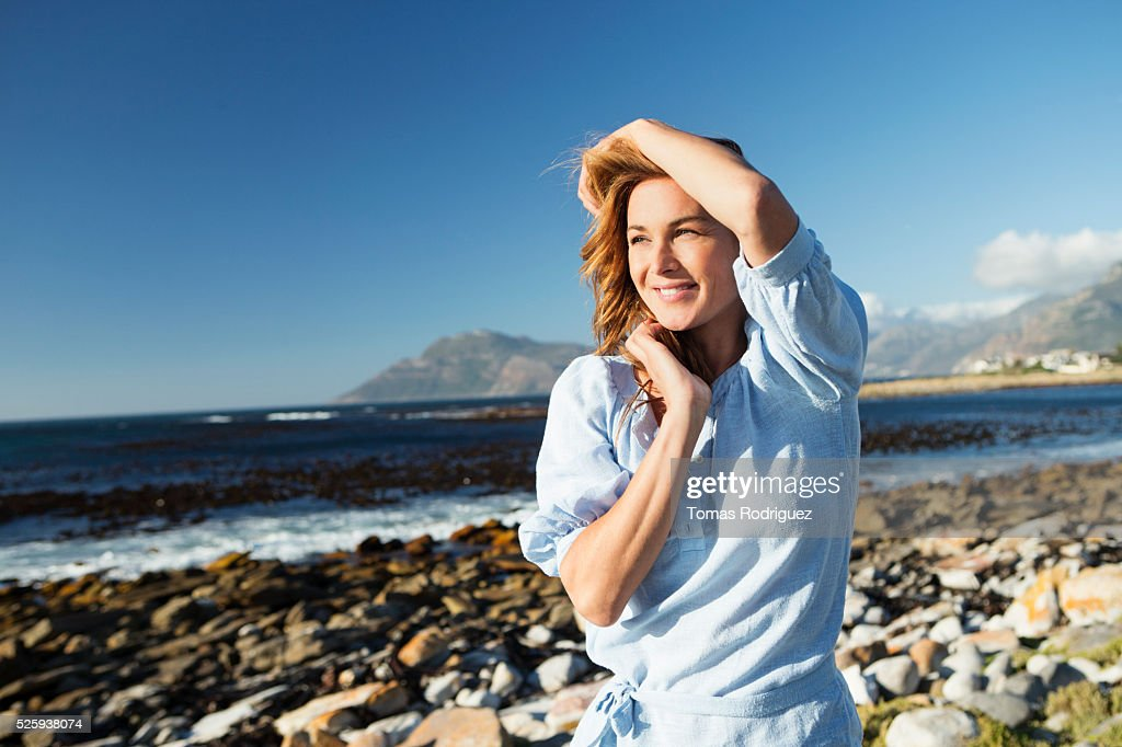 Young woman standing on sea shore : Stock-Foto