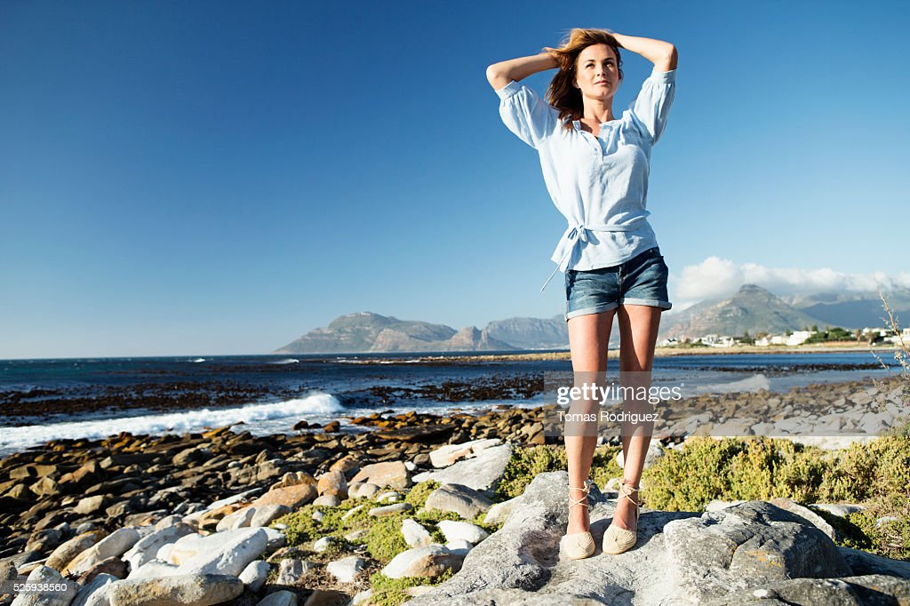 Young woman standing on sea shore : Stock Photo