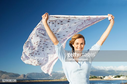 Young woman standing on sea shore with scarf blown by wind : Foto de stock