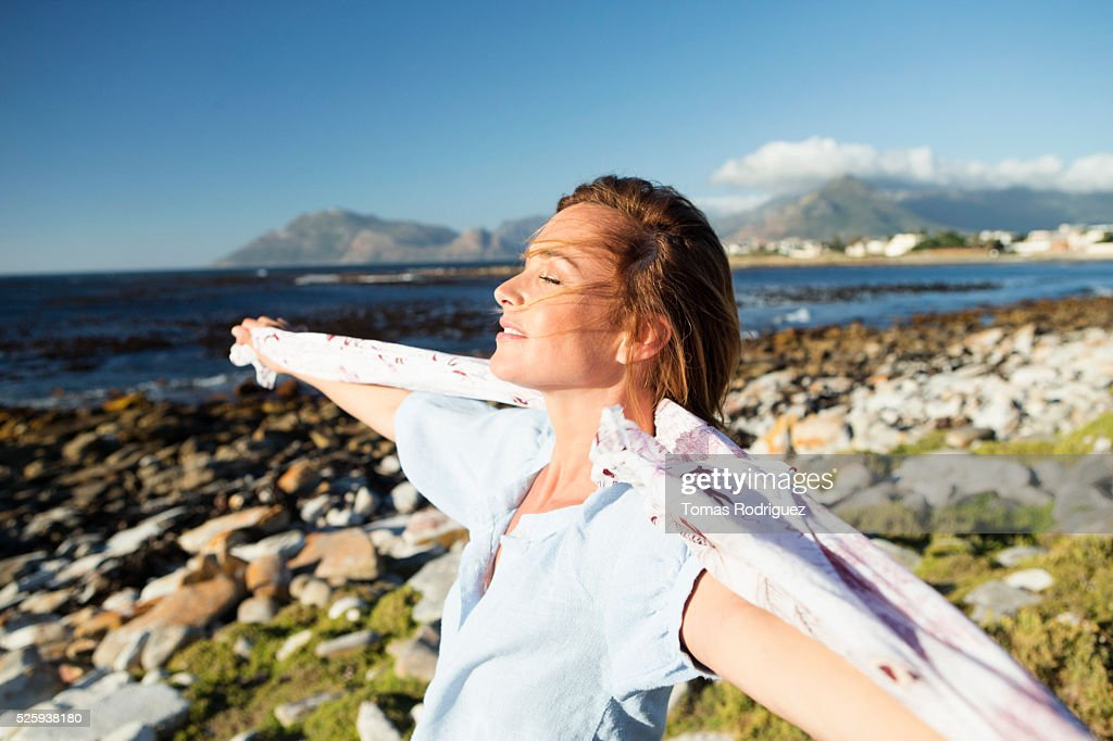 Young woman standing on sea shore with scarf blown by wind : Stockfoto