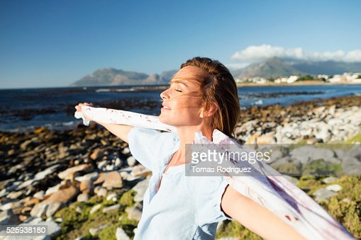 Young woman standing on sea shore with scarf blown by wind : ストックフォト