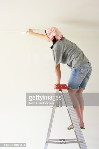 Young woman standing on step ladder, painting wall, side view