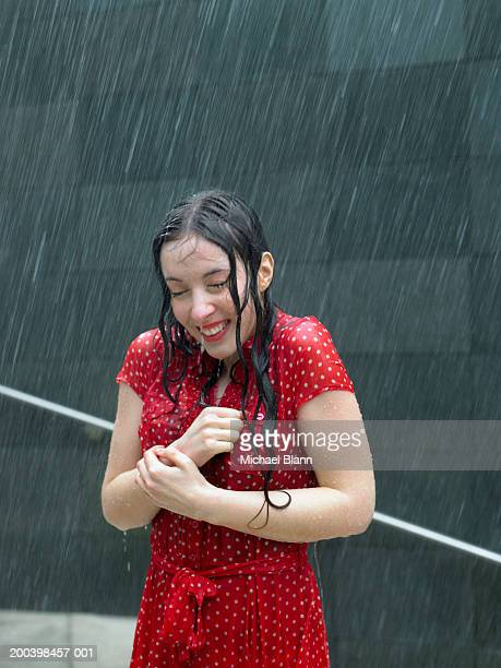 Young woman standing on steps in rain, eyes closed, smiling
