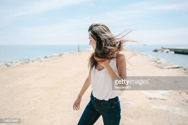 Young woman standing on the beach, enjoying wind