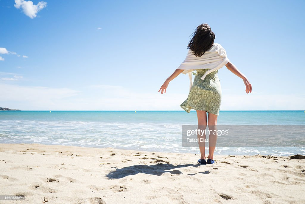 Young woman standing on the shore : Stock Photo