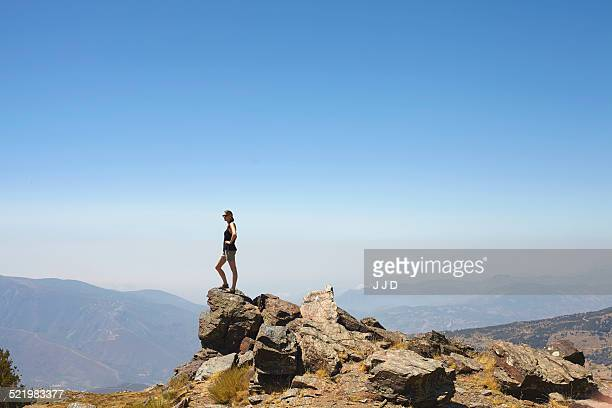 Young woman standing on top of rocks gazing at view, Sierra Nevada, Andalucia Granada, Spain