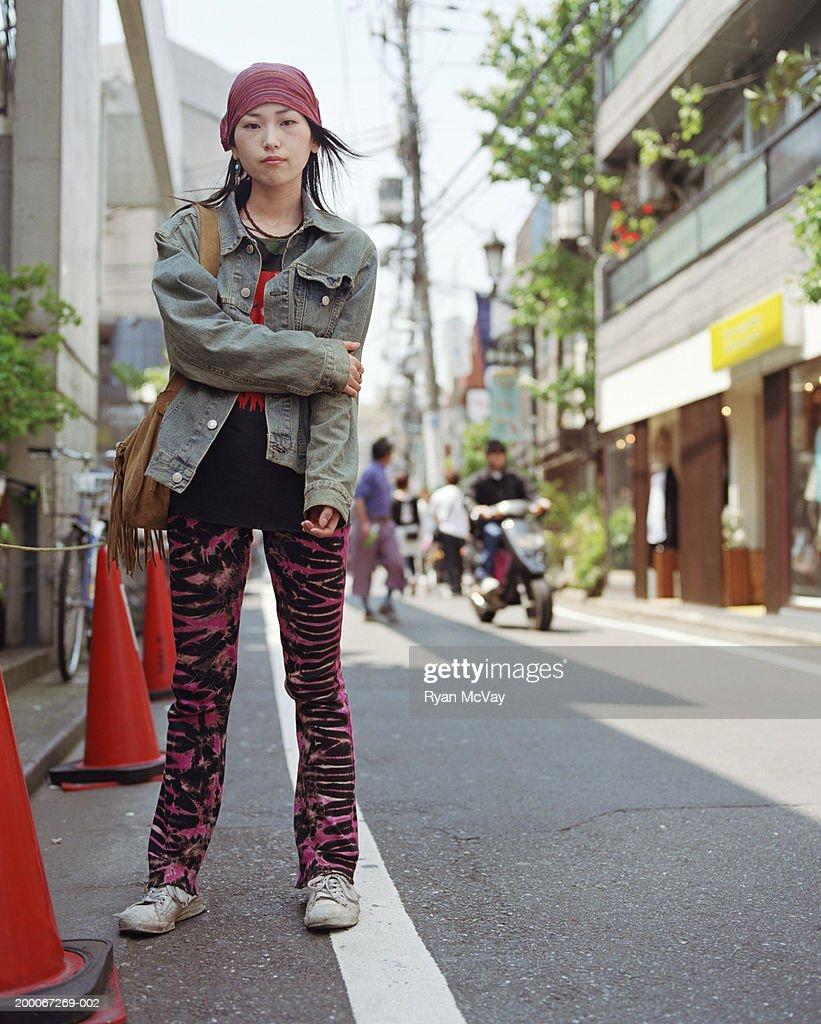 Young woman standing on urban sidewalk, portrait : Stock Photo
