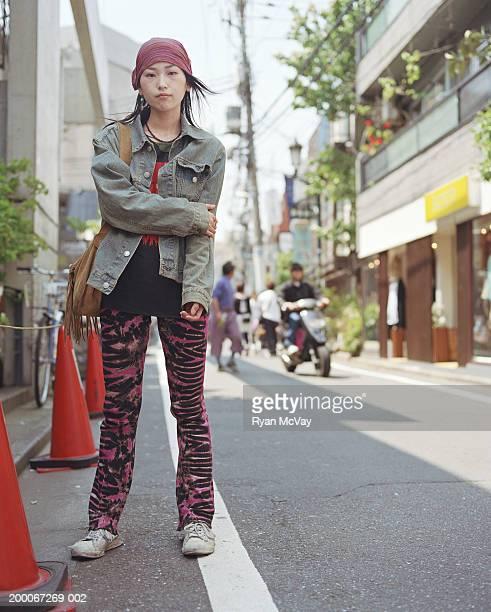 Young woman standing on urban sidewalk, portrait