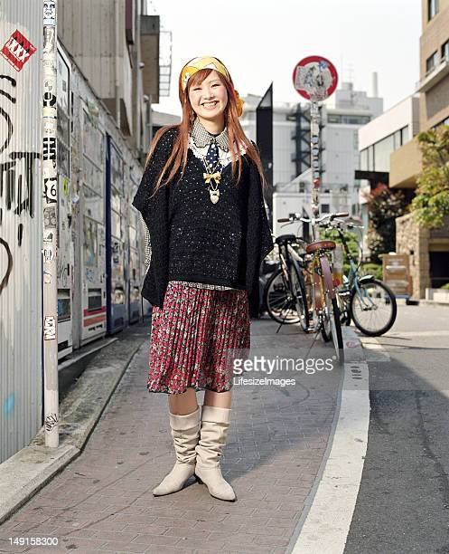 Young woman standing on urban sidewalk, smiling, portrait