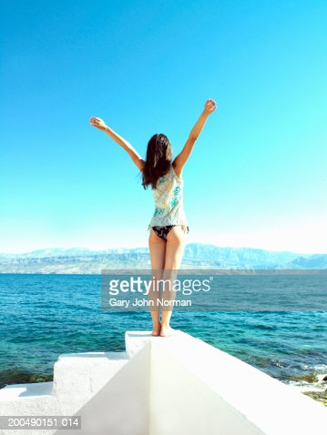 Young woman standing on white wall by sea, arms outstretched rear view : Stock Photo