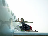Young woman standing on wing of airplane, knocking on window