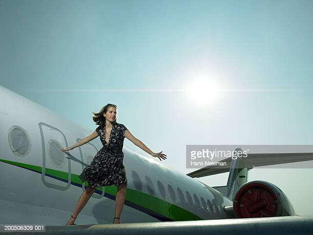 Young woman standing on wing of airplane