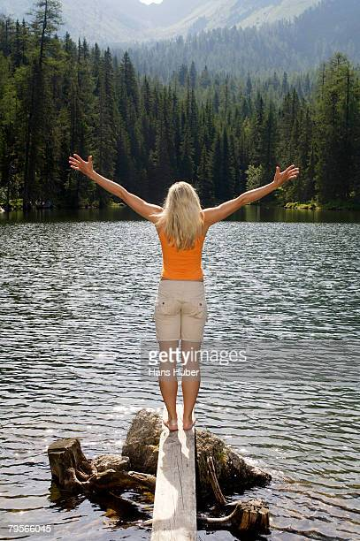 'Young woman standing on wooden plank at lake, arms out'