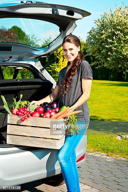 Young woman standing outdoor with box of vegetables