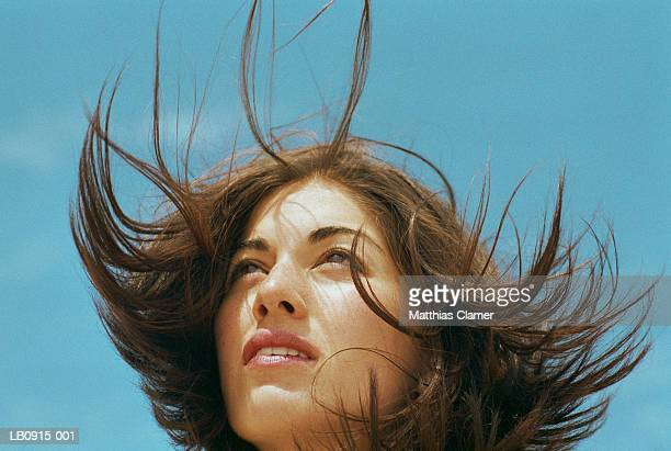 Young woman standing outdoors, hair blowing, close-up