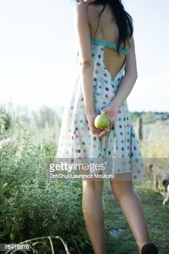 Young woman standing outdoors, holding apple behind back, cropped