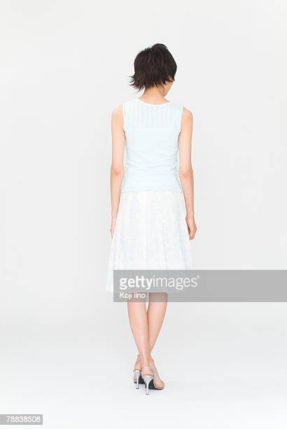 Young woman standing, rear view