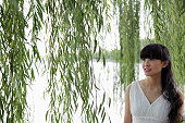 Young woman standing under a willow tree