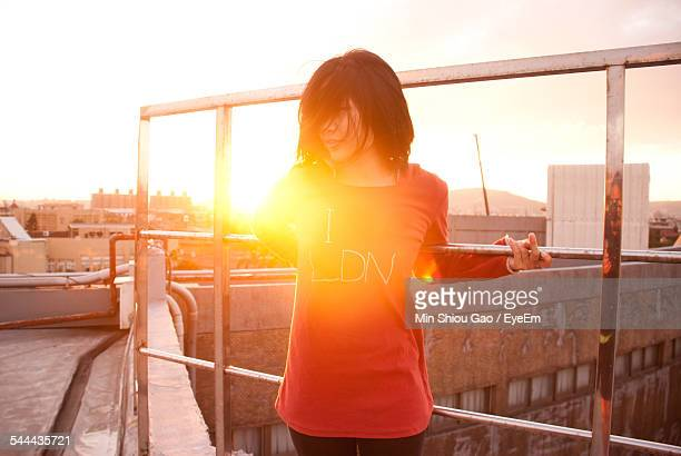 Young Woman Standing While Holding Railing On Building Terrace At Morning