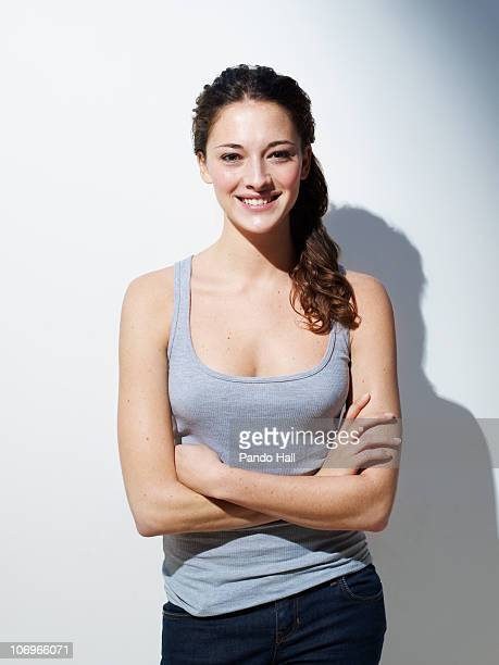 Young woman standing with arms crossed, smiling
