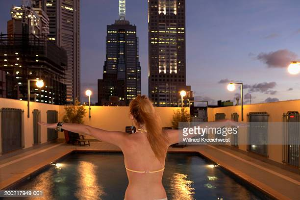 Young woman standing with arms outstretched in front of swimming pool
