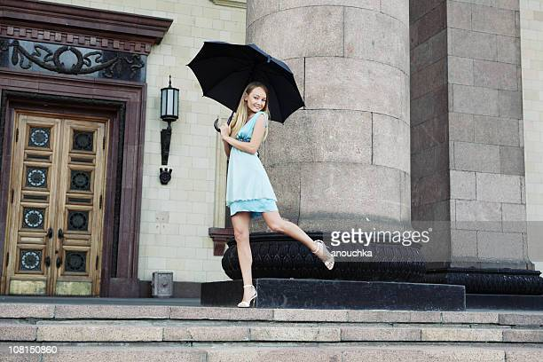 Young Woman Standing with Black Umbrella at Entrace to Building