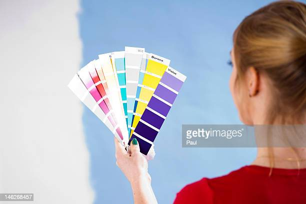 Young woman standing with color samples at a wall