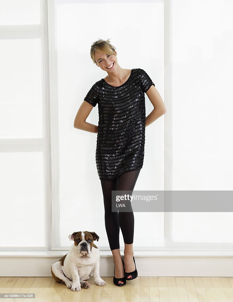 Young woman standing with dog, smiling, portrait : Stock Photo