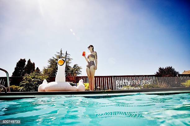 Young woman standing with drink on pool deck