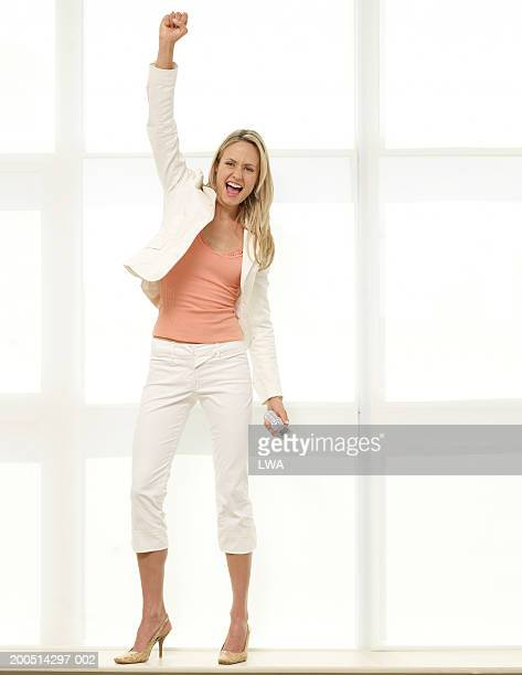 Young woman standing with hand raised, shouting
