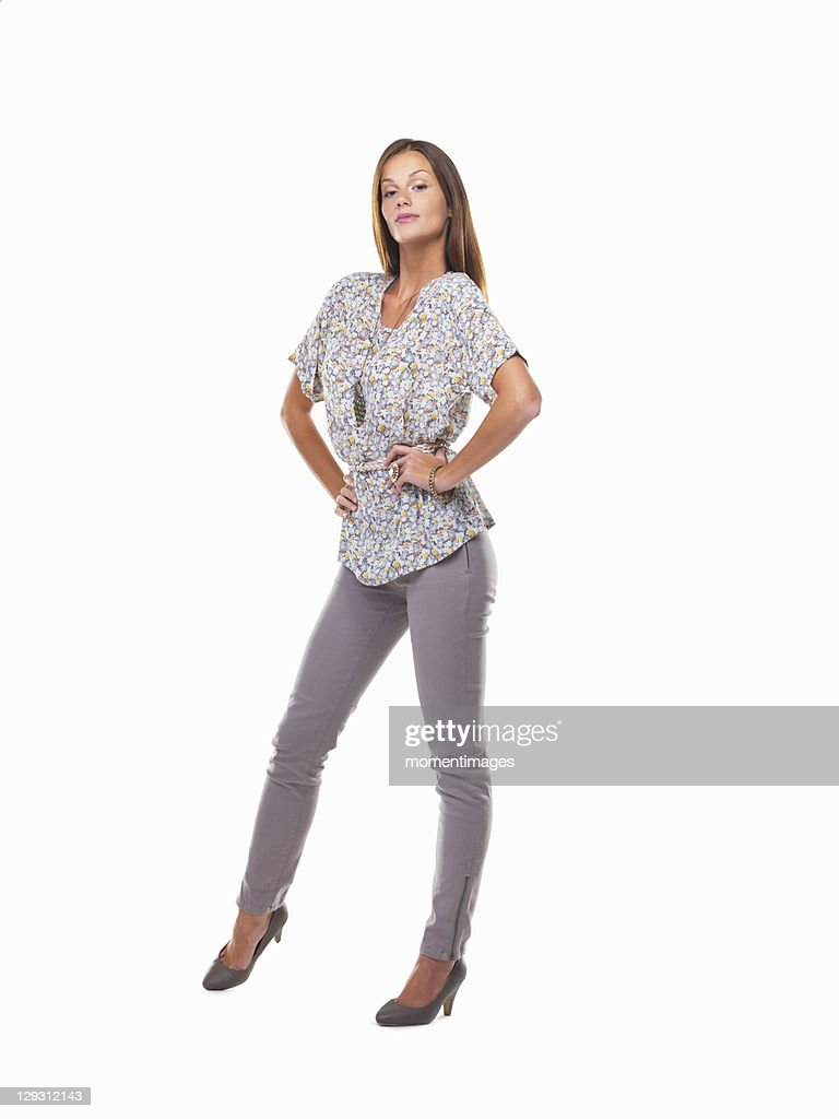 Young woman standing with hands on hips and smiling against white background : Stock Photo