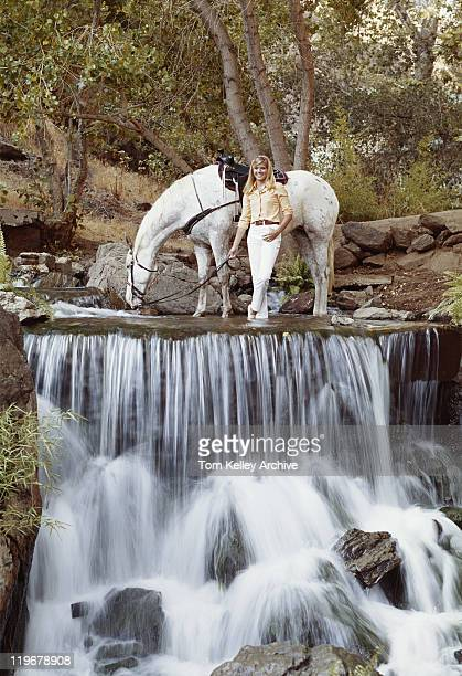 Young woman standing with horse at edge of waterfall, smiling
