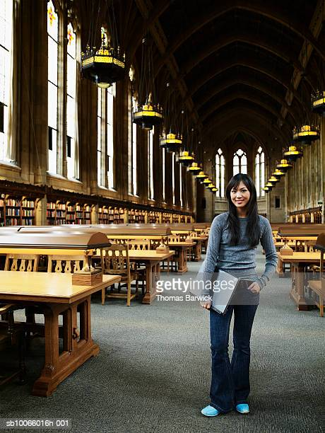 Young woman standing with laptop in university library, smiling