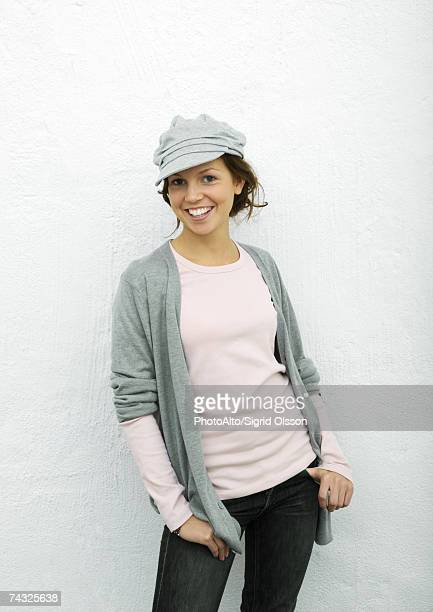 Young woman standing with thumbs in pockets, portrait