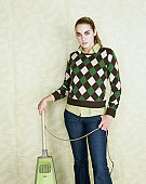 Young woman standing with vacuum cleaner, portrait