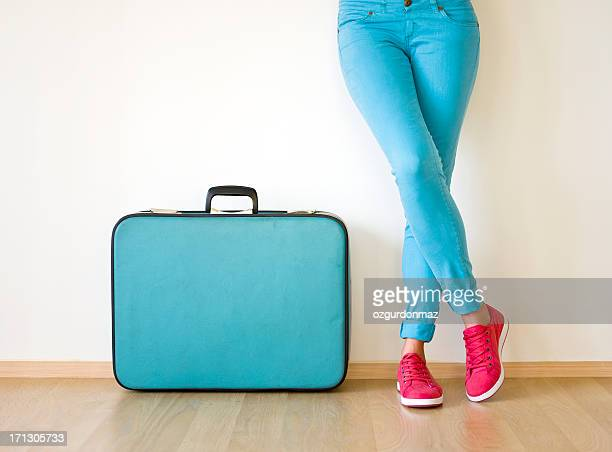 Young woman stands beside suitcase