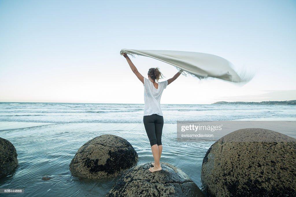 Giovane donna si trova sulla Boulder, mostra coperta in aria : Foto stock