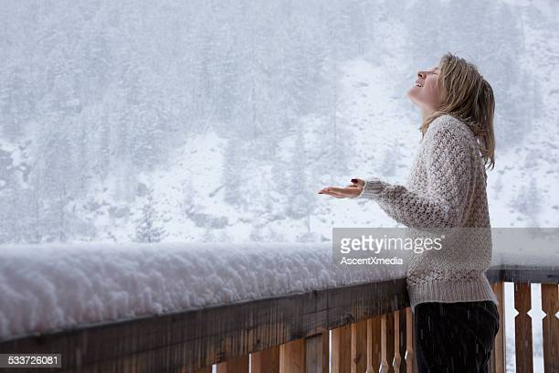 Young woman stands on deck, watches snowflakes fall during snows